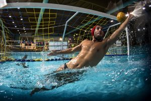 A water polo goalkeeper and the ball going into the net of the goal.